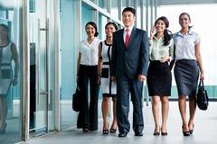 Asiatisches Geschäftsteam, das in Büro marschiert Lizenzfreie Stockbilder