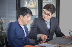 Asiatisches Geschäftsteam, das Dokument bei der Sitzung bespricht lizenzfreie stockfotografie