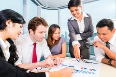 Asiatisches Geschäftsteam, das Bericht bespricht Stockfoto