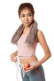 Asiatisches gesundes Mädchen mit dem Apfel, der ihre Taille misst Stockbilder