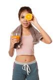 Asiatisches gesundes Mädchen mit Orangensaft und Orange über ihrem Auge Stockbild
