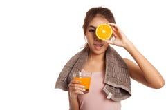 Asiatisches gesundes Mädchen mit Orangensaft und Orange über ihrem Auge Stockfotografie