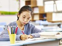 Asiatisches grundlegendes Schulmädchen, das Hausarbeit im Klassenzimmer tut Lizenzfreies Stockfoto