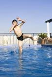 Asiatisches Junge jumpin in Swimmingpool Lizenzfreie Stockfotografie