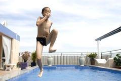 Asiatisches Junge jumpin in Swimmingpool Stockbilder
