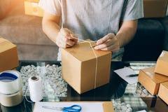Asiatisches junges Jugendlicher owener des verpackenden Produktes des Kleinbetriebs in den Kästen, die es für Lieferung vorbereit lizenzfreies stockfoto
