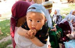 Asiatisches Kind, das auf den Armen seiner Mutter während eines Familienurlaubs sitzt Lizenzfreies Stockbild