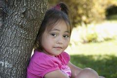 Asiatisches Kind, das auf einem Baum sich lehnt Lizenzfreie Stockfotografie