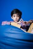 Asiatisches Kind, das auf einer Bohnentasche mit den Händen in-vorder sitzt Stockbild