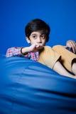 Asiatisches Kind, das auf einer Bohnentasche mit den Händen in-vorder sitzt Lizenzfreies Stockfoto