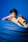 Asiatisches Kind, das auf einer Bohnentasche mit den Händen in-vorder sitzt Stockbilder