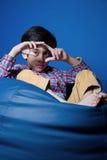 Asiatisches Kind, das auf einer Bohnentasche mit den Händen in-vorder sitzt Fokus auf Händen Stockfotos