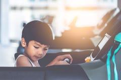 Asiatisches Kind, das auf Tretmühle mit Sonnenaufflackern läuft stockfotografie