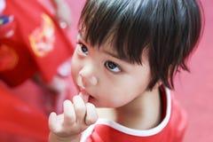 Asiatisches Kind, das Daumen im Kleiderrotstoff saugt Lizenzfreies Stockbild