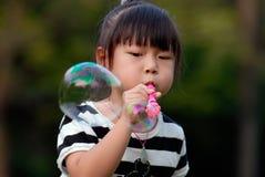 Asiatisches Kind, das durchbrennenluftblasen spielt Stockfotografie