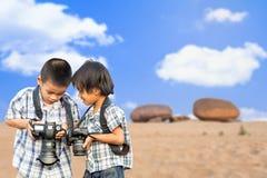 Asiatisches Kind, das Fotokamera hält Stockbild