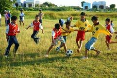 Asiatisches Kind, das Fußball, Leibeserziehung spielt Lizenzfreie Stockfotos