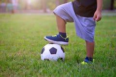 Asiatisches Kind, das Fußball oder Fußball im Park spielt Schritt auf dem Ball lizenzfreie stockfotografie