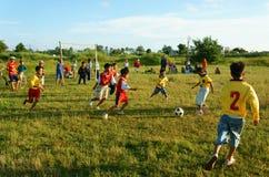 Asiatisches Kind, das Fußball, Leibeserziehung spielt Stockbilder