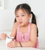 Asiatisches Kind, das Jogurt isst Stockbild