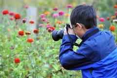 Asiatisches Kind, das Makrophoto macht Stockfotos