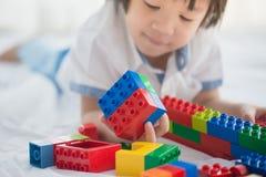 Asiatisches Kind, das mit bunten Baublöcken spielt lizenzfreies stockbild