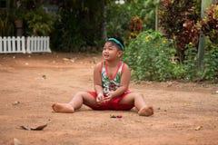 Asiatisches Kind, das mit Sand und Ball im Spielplatz spielt Stockbilder
