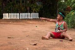 Asiatisches Kind, das mit Sand und Ball im Spielplatz spielt Stockbild