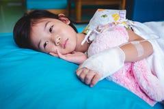 Asiatisches Kind der Krankheit ließ im Krankenhaus mit salzigem iv-Tropfenfänger an Hand zu Gesundheitswesengeschichten stockbilder