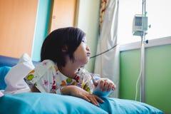 Asiatisches Kind der Krankheit lie? im Krankenhaus mit salzigem iv-Tropfenf?nger an Hand zu Gesundheitswesengeschichten lizenzfreies stockfoto