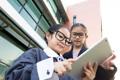 Asiatisches Kind des Geschäfts, das Tablette verwendet Stockbilder