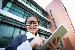 Asiatisches Kind des Geschäfts, das Tablette verwendet Stockbild