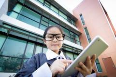 Asiatisches Kind des Geschäfts, das Tablette verwendet Stockfoto