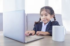 Asiatisches Kind im Geschäftsgebrauchslaptop mit heißem ceremic Becher lizenzfreie stockfotografie