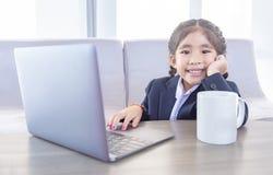 Asiatisches Kind im Geschäftsgebrauchslaptop mit heißem ceremic Becher stockfotos