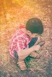 Asiatisches Kind mit Lupe am Park im Urlaub Ausbildung Lizenzfreie Stockfotografie