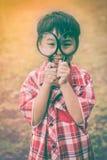 Asiatisches Kind mit Lupe am Park im Urlaub Ausbildung Stockfotografie