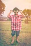 Asiatisches Kind mit Lupe am Park im Urlaub Ausbildung Lizenzfreies Stockfoto