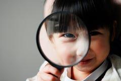 Asiatisches Kind mit Vergrößerungsglas Stockbilder