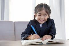 Asiatisches Kinderhartes Lernen und -zeichen mit Lehrbuch lizenzfreies stockfoto
