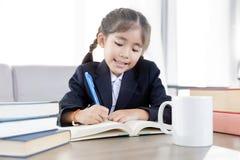 Asiatisches Kinderhartes Lernen und -zeichen mit Lehrbuch stockbilder