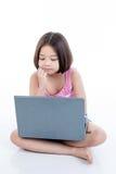 Asiatisches Kindermädchen, das Laptop und das Denken verwendet Stockbilder