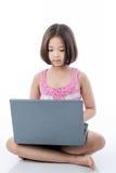 Asiatisches Kindermädchen, das Laptop verwendet Stockbilder