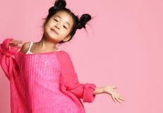 Asiatisches Kindermädchen in der rosa Strickjacke, in den weißen Hosen und in den lustigen Brötchen ist in Mode Haltung und Läche stockfoto