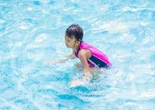 Asiatisches Kindermädchen im Swimmingpool Lizenzfreie Stockfotos