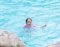 Asiatisches Kindermädchen im Swimmingpool mit dem Finger-Zeigen Lizenzfreie Stockfotografie