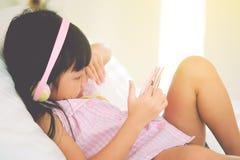 Asiatisches Kindermädchen sind- süchtig machend, Tablette und Handys spielend stockfoto