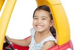 Asiatisches Kindermädchen, das Spielzeugautogelb fährt Stockfoto