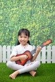 Asiatisches kleines chinesisches Mädchen, das auf Gras sitzt und mit guit spielt lizenzfreies stockbild