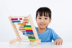 Asiatisches kleines chinesisches Mädchen, das bunten Abakus spielt Lizenzfreie Stockfotografie
